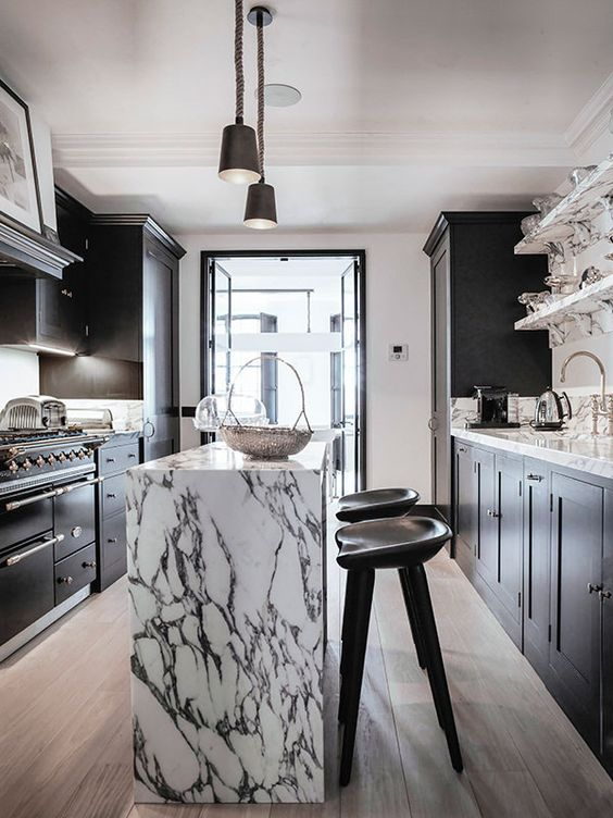 a sophisticated black kitchen with a white stone backsplash and countertops plus black lamps and stools is wow