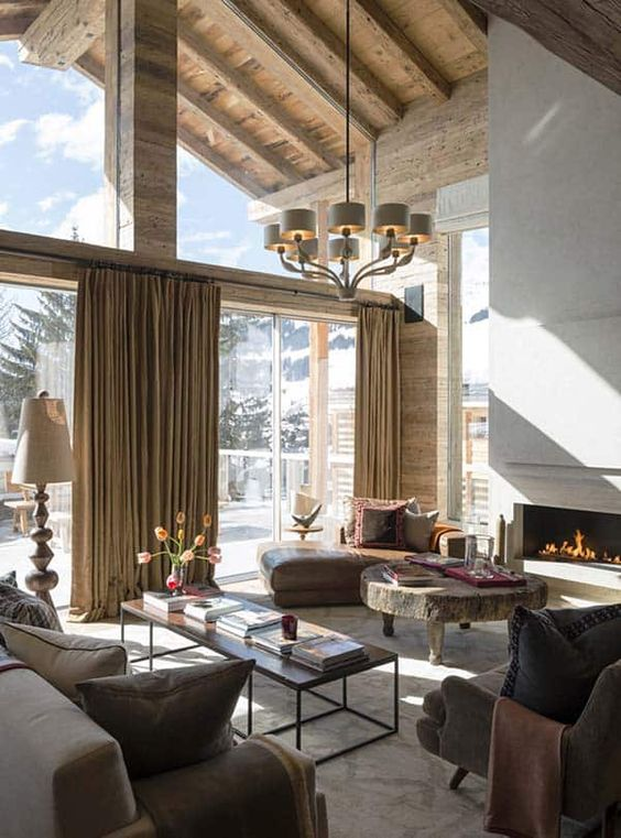 a sophisticated chalet living room in neutrals, with a fireplace, stylish furniture, a round table and a glazed wall