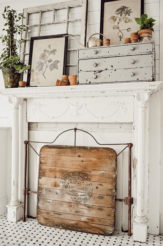 a spring farmhouse mantel and fireplace with potted greenery, a cactus, a wooden screen and artworks is a lovely space