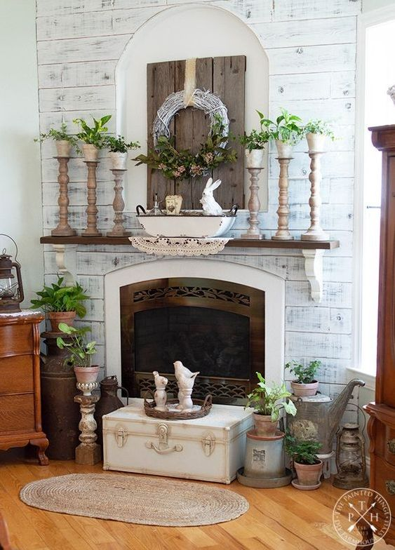 a spring farmhouse mantel with wooden candleholders with potted greenery, potted plants around the fireplace and a greenery and floral wreath