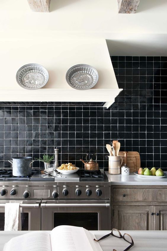 a stained wooden kitchen, a creamy hood, a black glossy tile backsplash and stainless steel appliances is bold and cozy