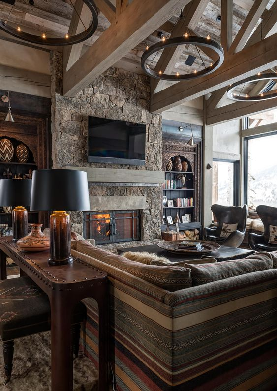 a stylish chalet living room clad with wood, with a stone fireplace, boho and modern furniture and round chandeliers