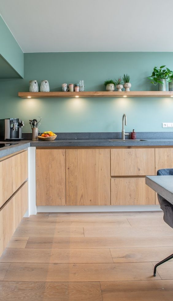 a stylish contemporary kitchen with light stained cabinets, green walls and a concrete countertop plus a floating shelf with lights