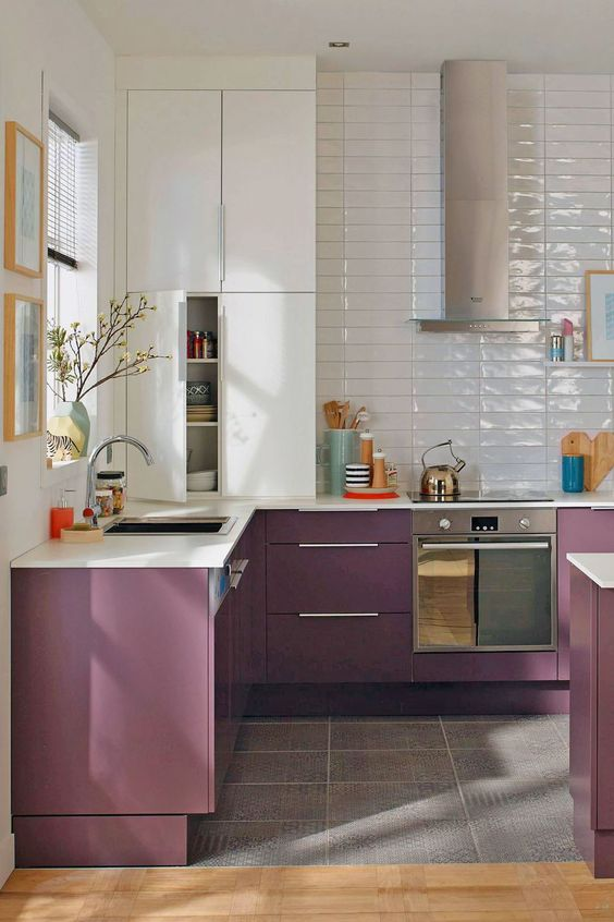 a stylish contemporary kitchen with white and purple cabinets, glossy white skinny tiles and stainless steel appliances