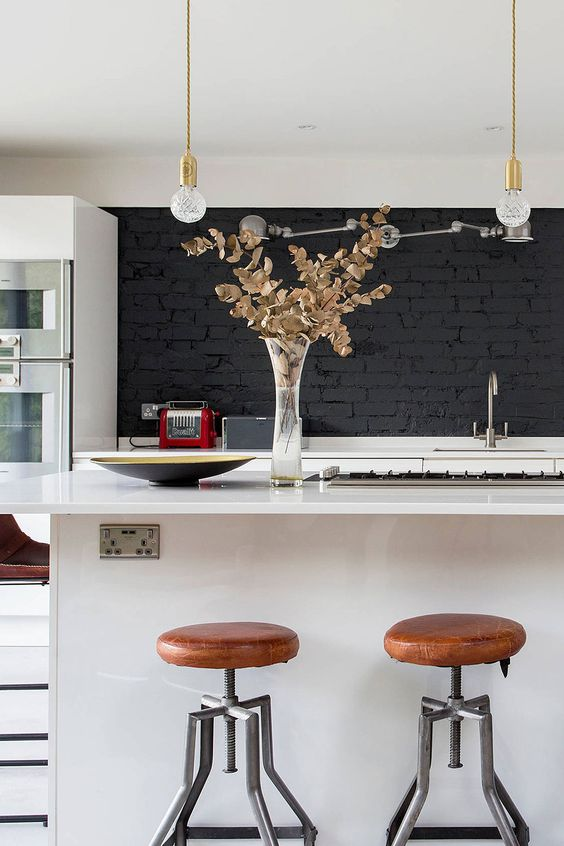 a stylish contemporary white kitchen with a black brick backsplash, pendant bulbs and touches of gold is chic and bold
