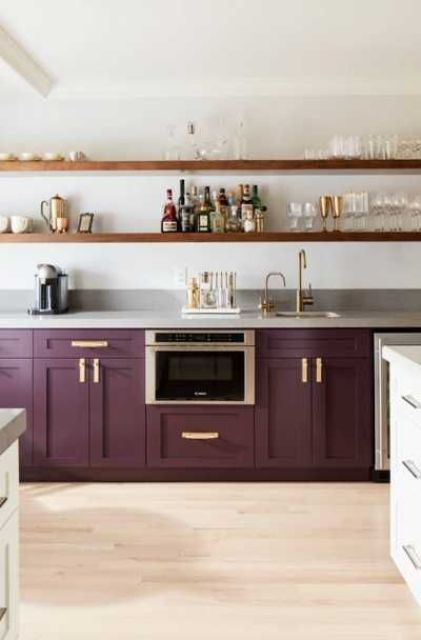 a stylish deep purple kitchen with vintage cabinets, grey stone countertops and long open shelves plus gold touches