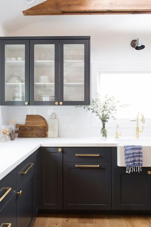 a stylish farmhouse kitchen with graphite grey cabinets, brass handles and white quartz countertops and a white tile backsplash