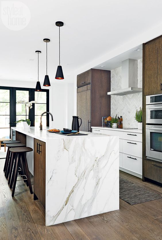 a stylish kitchen with dark stained cabinets and a kitchen island plus a lovely white stone waterfall countertop that adds chic