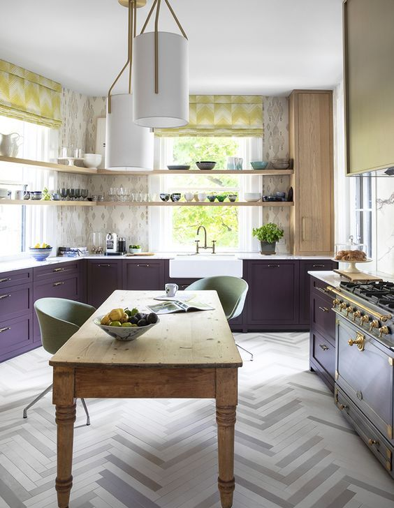 a stylish kitchen with deep purple cabinets, open shelves, a vintage cooker and bold textiles plus a vintage wooden table