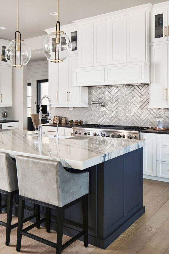 a stylish kitchen with white cabinets and a navy ktichen island, a white quartz countertop, a herringbone backsplash and glass pendant lamps