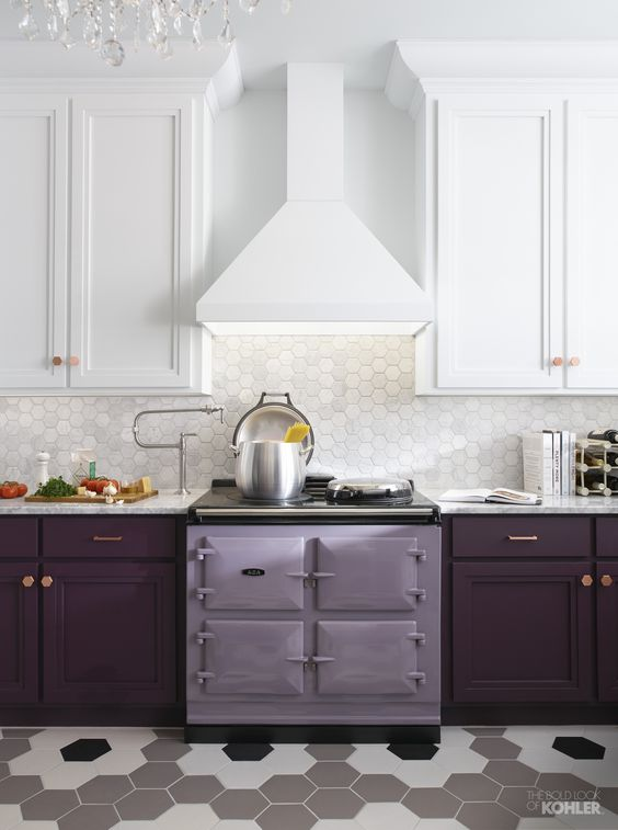 a stylish kitchen with white upper cabinets and plum lower ones, a lilac stove and a white hex tile backsplash