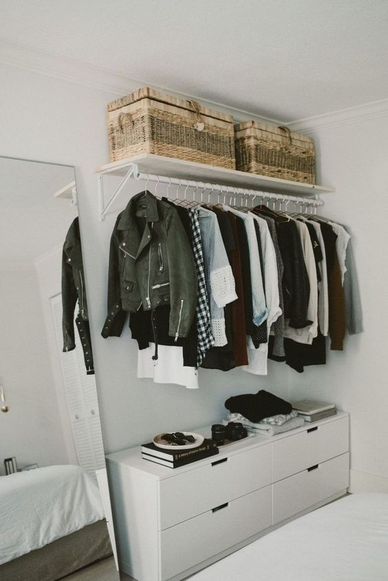 a stylish makeshift closet with baskets for storage on top and an additional white dresser for smaller things under it