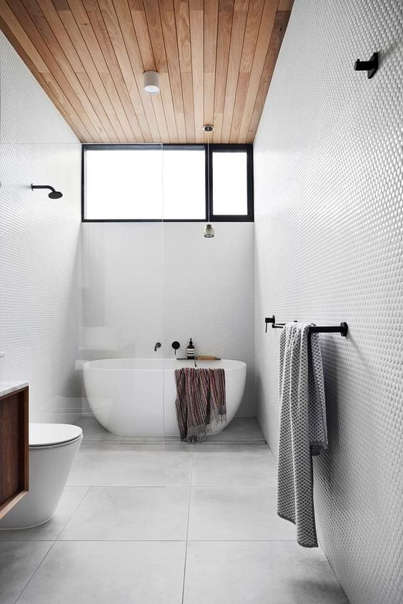 a stylish minimal bathroom clad with neutral tiles, a wooden ceiling and chic appliances plus black fixtures