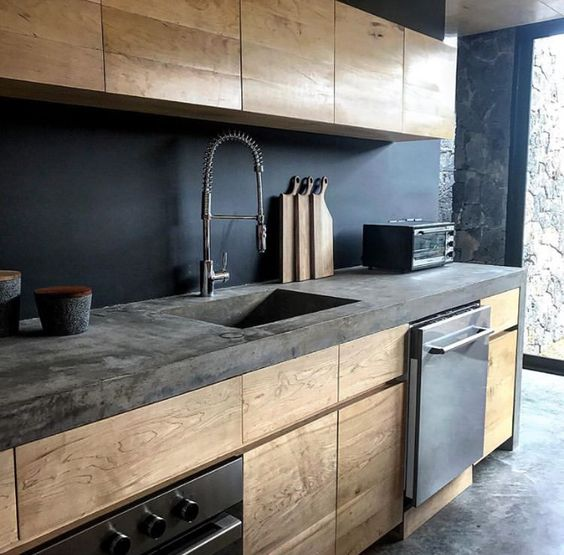 a stylish minimalist kitchen with light stained cabinets, a black backsplash and a concrete countertop feels industrial, too