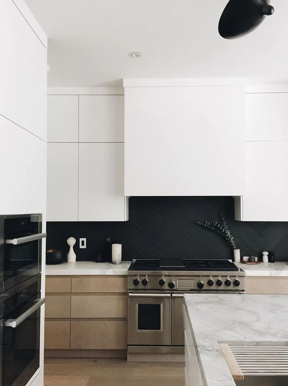 a stylish minimalist kitchen with light stained cabinets, white upper ones, a matte black herringbone backsplash and white quartz countertops