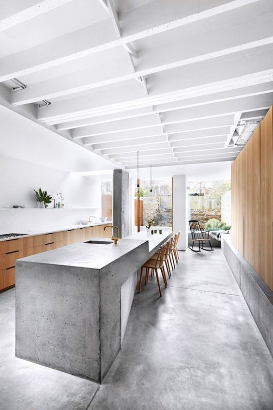 a stylish minimalist kitchen with pretty cabinets and a large kitchen island with a concrete waterfall countertop and brass fixtures