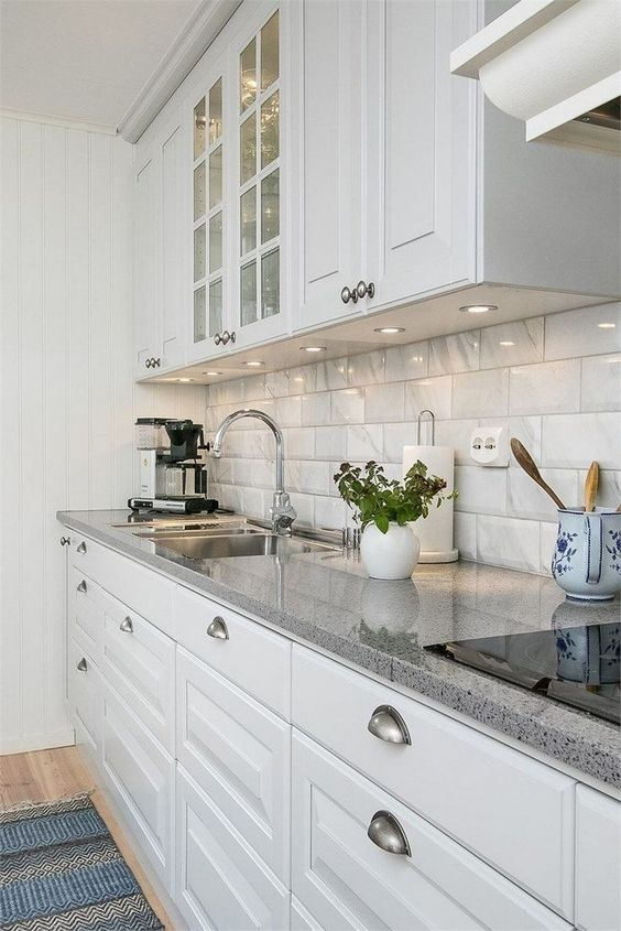 a stylish modern kitchen in white, with glossy tiles on the backsplash and grey granite countertops plus built-in lights is chic