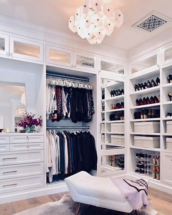 a stylish vintage-inspired closet with drawers, clothes holders, open shelves for storign shoes and boxes plus a cool chandelier and an ottoman