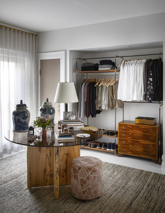 a stylish walk-in closet with a makeshift closet, open shelves for jumpers and shoes, a dresser for small stuff is veyr cool