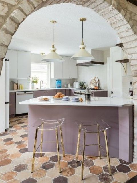 a stylish white and purple kitchen with white coutnertops and a backsplash, clear acrylic stools on gold legs