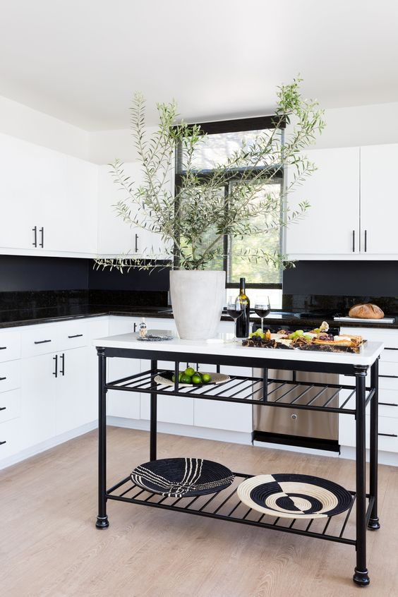 a stylish white kitchen with glossy black tiles and a chalkboard backsplash, a black and white kitchen island is very chic