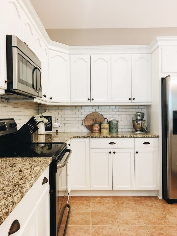 a stylish white kitchen with granite countertops, a white tile backsplash and black knobs and fixtures