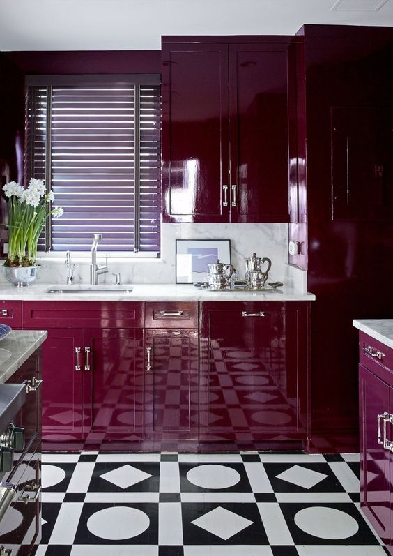 a sumptuous plum kitchen with a white stone countertop and a backsplash, a patterned tile floor and some blooms