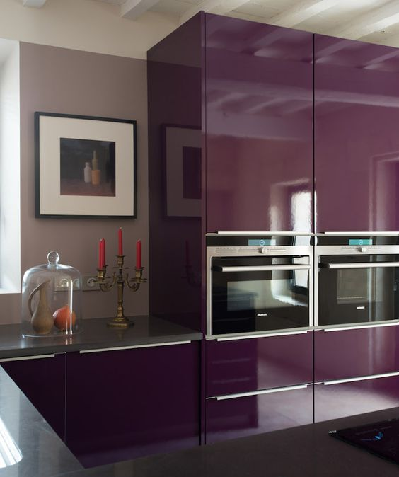 a sumptuous purple kitchen wiht a glossy finish, grey stone countertops and pretty art is chic and bold