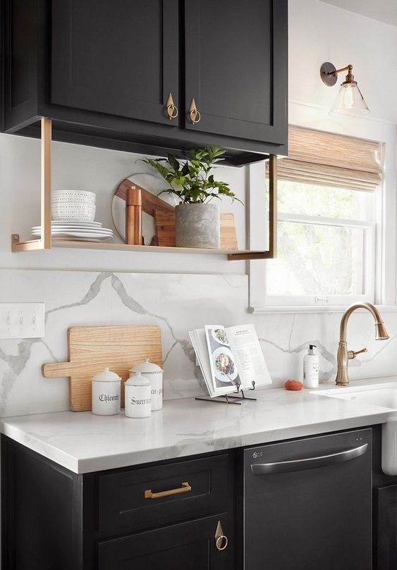 a super elegant black kitchen with white quartz countertops and a backsplash, brass touches and fixtures and woven shades on the windows