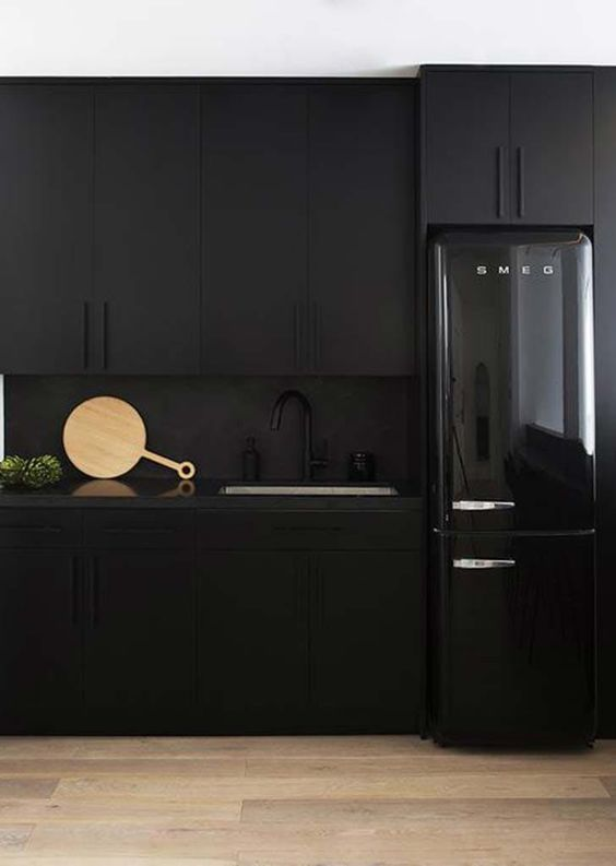 a total black kitchen with matte cabinets, a matte backsplash and a shiny and glossy fridge is a bold idea