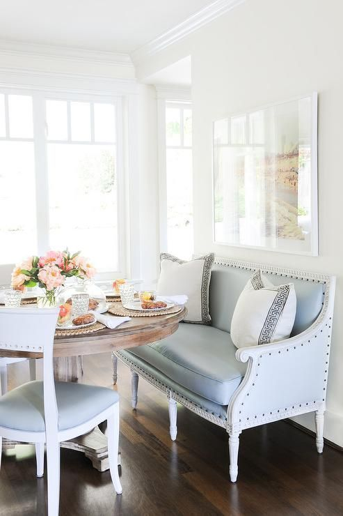 a vintage and refined blue loveseat with white pillows is used as an upholstered bench in the dining zone