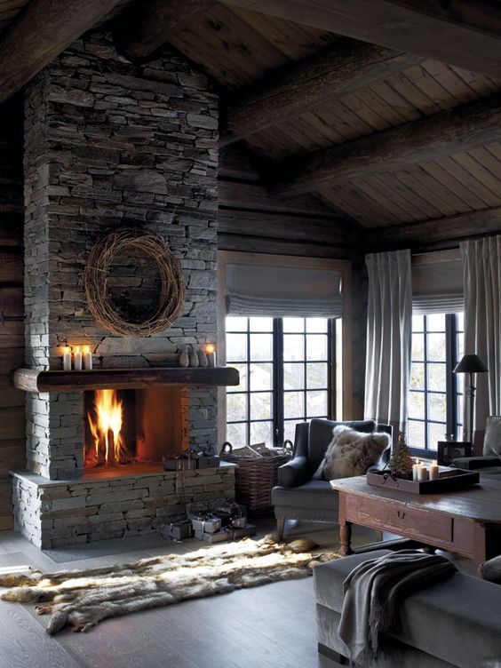 a vintage chalet living room with wooden walls and a ceiling, a stone fireplace and faux fur accessories