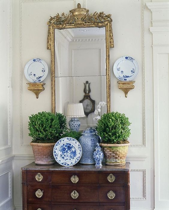 a vintage console table with potted greenery, chinoiserie, a mirror in a vintage frame and a pretty lamp