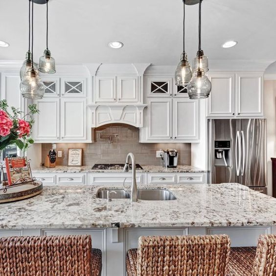 a vintage creamy kitchen with a grey tile backsplash, grey granite countertops, clusters of glass pendant lamps and woven stools