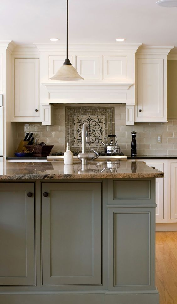 a vintage creamy kitchen with a grey tile backsplash with a mosaic, a grey kitchen island and beige granite coutnertops plus a vintage lamp