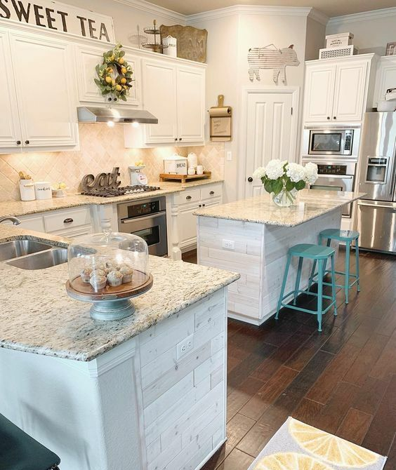 a vintage creamy kitchen with a herringbone backsplash and grey granite countertops, built-in lights and turquoise stools