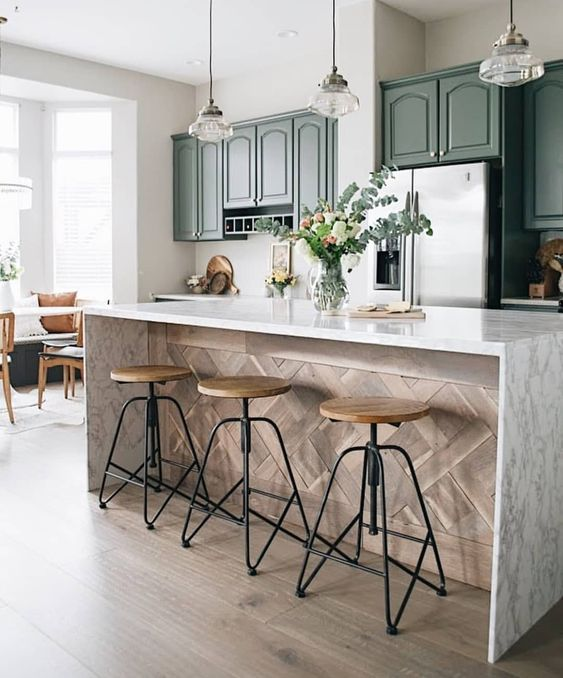a vintage green kitchen with a kitchen island with a white stone countertop and wood cladding it plus elegant pendant lamps