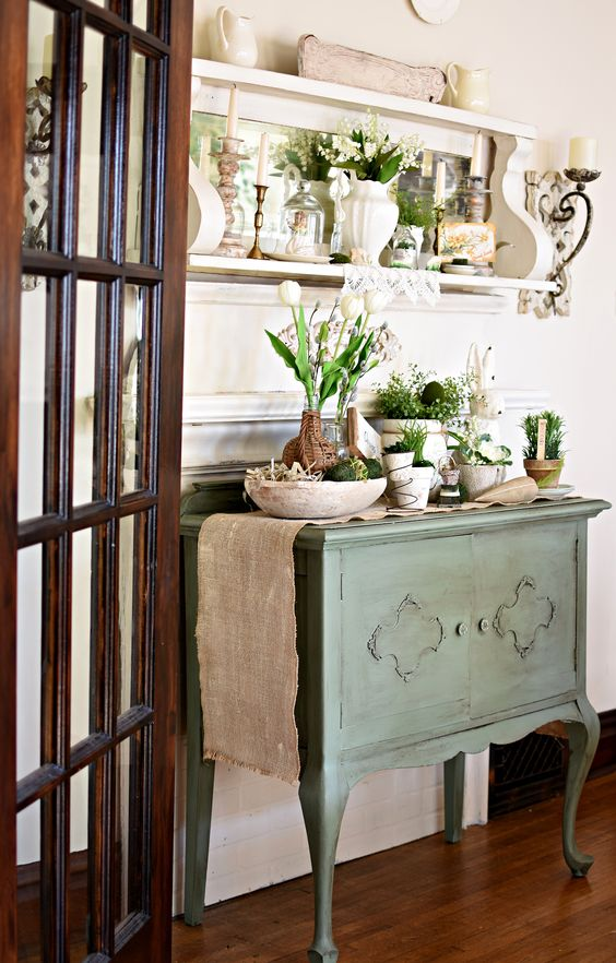 a vintage green spring console table with potted greenery and white blooms, with a shelf with a mirror and some candles