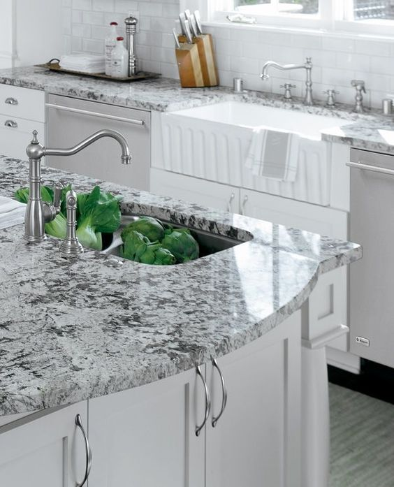 a vintage grey and white kitchen with grey granite countertops and vintage fixtures is a stylish space to be