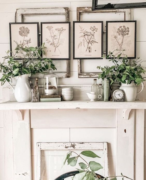 a vintage mantel with clocks, vases and jugs with greenery, botanical posters, cloches and jars is a chic idea