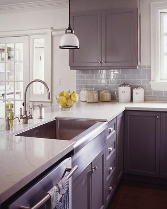 a vintage purple kitchen with white countertops, a grey subway tile backsplash and a pendant lamp
