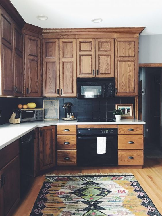 a vintage rustic kitchen with stained cabinetry, a black tile backsplash and white countertops plus a bold boho rug