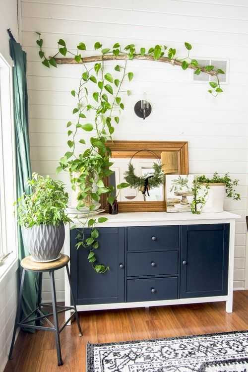 a vintage sideboard with some potted greenery, a stick and greenery installation over it and a grey planter with greenery
