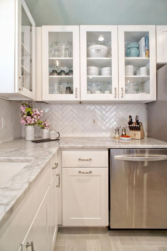 a vintage white kitchen with a herringbone backsplash and grey granite countertops plus vintage stainless steel fixtures