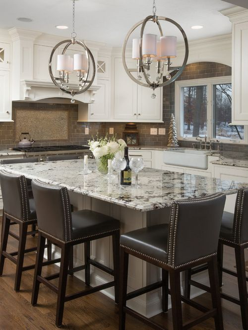 a vintage white kitchen with a taupe tile backsplash, white granite countertops and sphere pendant lamps plus brown stools
