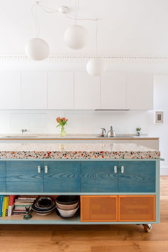 a vivacious kitchen with white sleek cabinets, a colorful kitchen island with a bright terrazzo countertop and pendant lamps