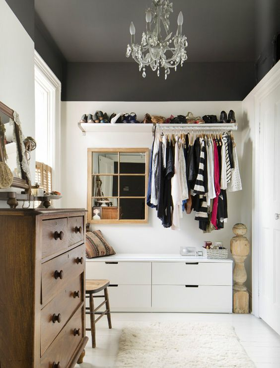 a walk-in closet with a couple of dressers, an open shelf for shoes, a holder for clothes and a mirror plus accessories storage