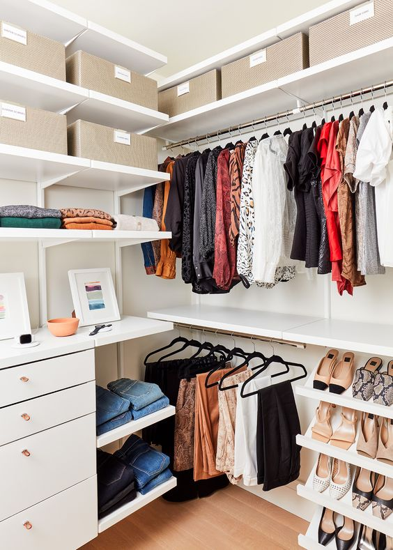 a walk in closet with open shelves, holders for clothes, open shoe shelves, shelves with boxes and drawers for small things