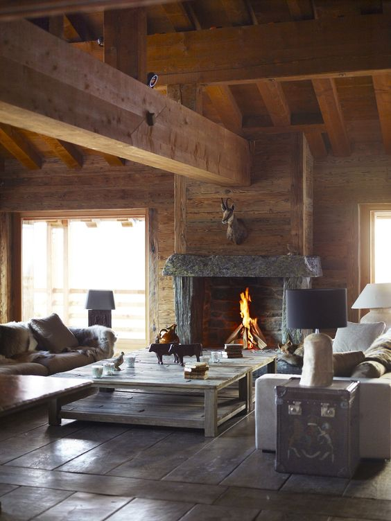 a warm and cozy chalet living room fully clad with wood, with modern furniture, low tables, a fireplace and elegant lamps