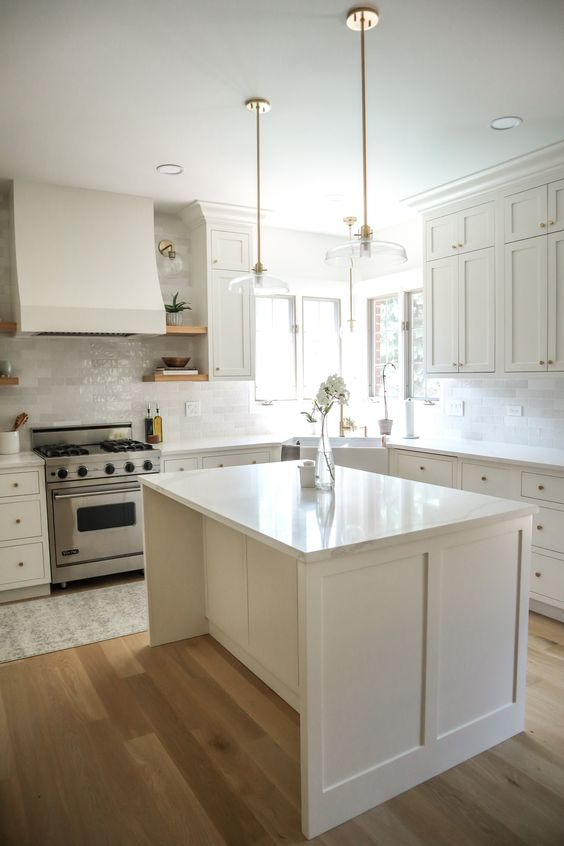 a welcoming and airy kitchen with white cabinets, a white marble tile backsplash and a small kitchen island plus quartz countertops